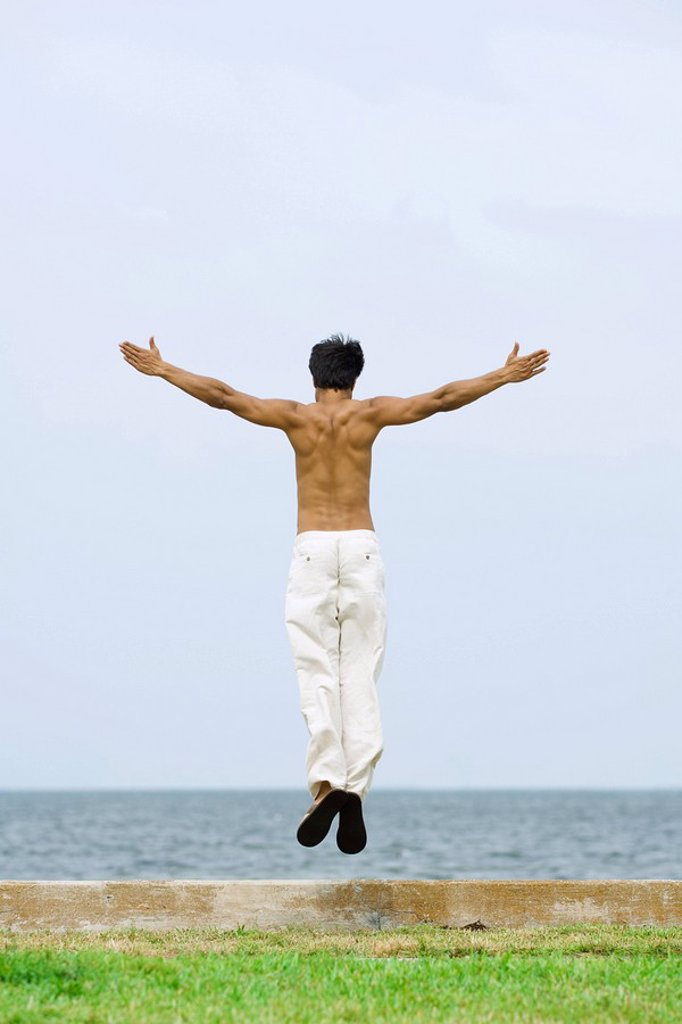 Man jumping in the air at the beach, arms outstretched, rear view : Stock Photo