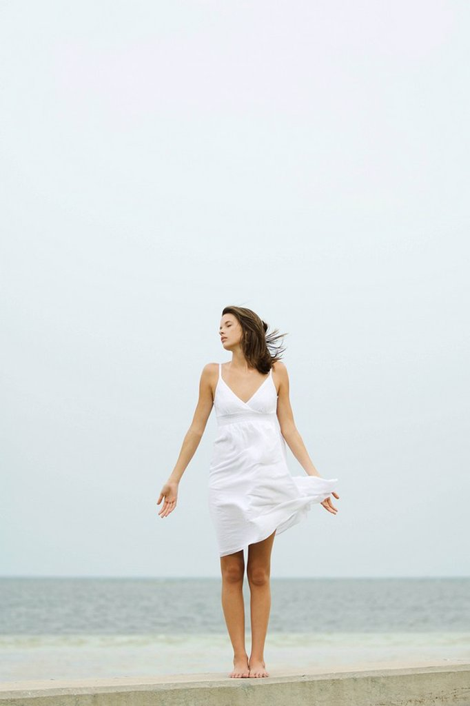 Teenage girl in sundress standing at the beach, tousled by wind, eyes closed : Stock Photo