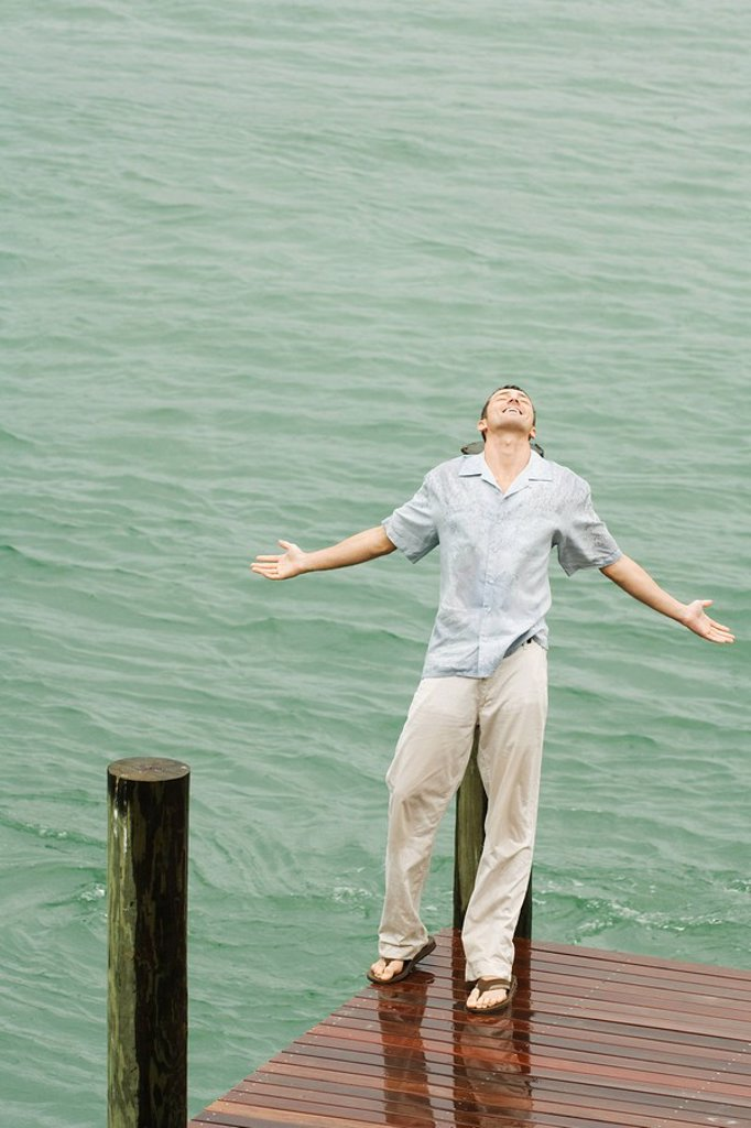 Stock Photo: 1569R-9033498 Man leaning back on pier in the rain, arms out, eyes closed, high angle view