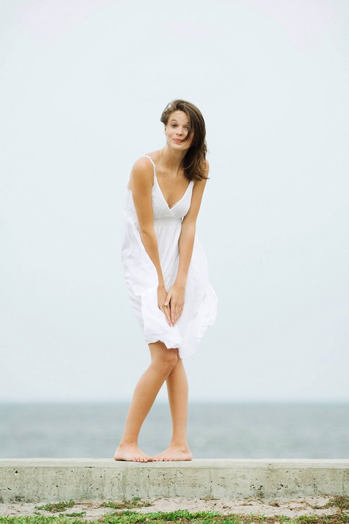 Teenage girl in front of the sea, bending over to hold skirt, tousled by wind, smiling at camera : Stock Photo