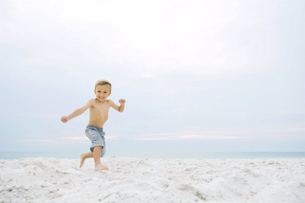 Little boy running at the beach, smiling at camera : Stock Photo