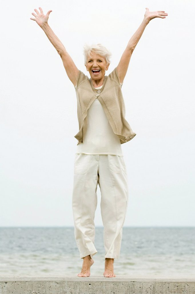 Stock Photo: 1569R-9033504 Senior woman standing on tiptoe at the beach, arms raised, smiling