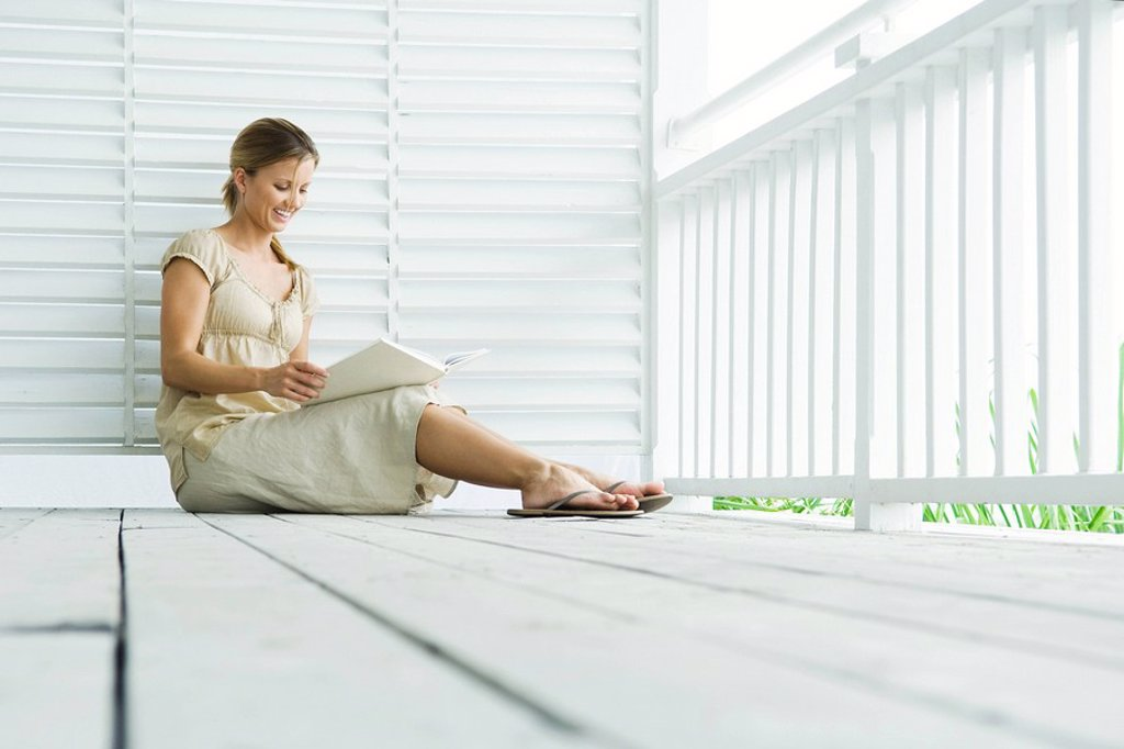Stock Photo: 1569R-9033505 Woman sitting on porch reading book, low angle view