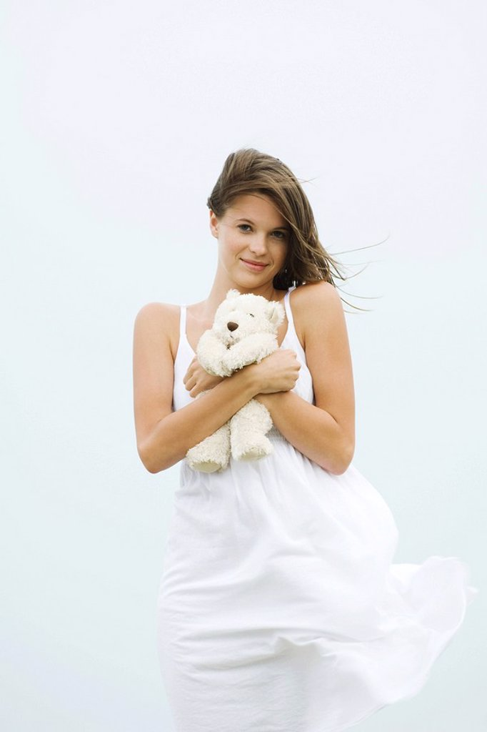 Stock Photo: 1569R-9033507 Teenage girl in sundress holding teddy bear, touseled by wind, smiling at camera