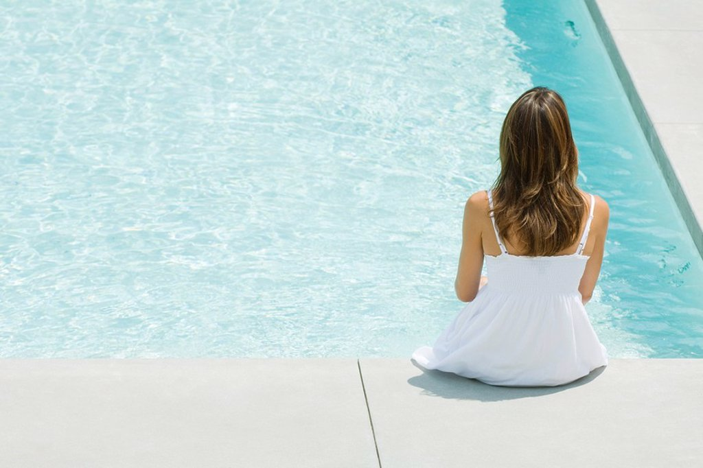 Woman sitting on edge of swimming pool, rear view, high angle : Stock Photo