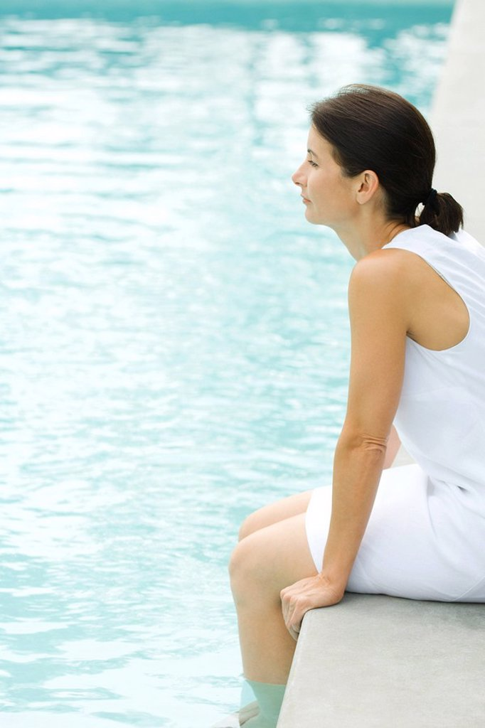 Stock Photo: 1569R-9033511 Woman sitting on edge of swimming pool, dipping feet in water, looking away