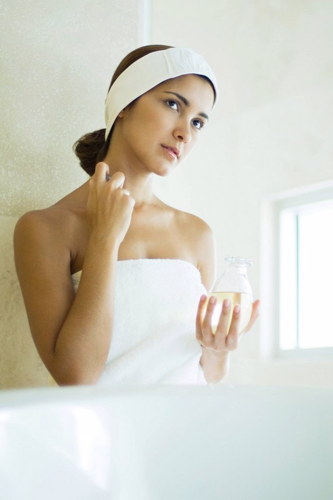 Stock Photo: 1569R-9033513 Young woman wrapped in towel applying perfume to neck, looking away
