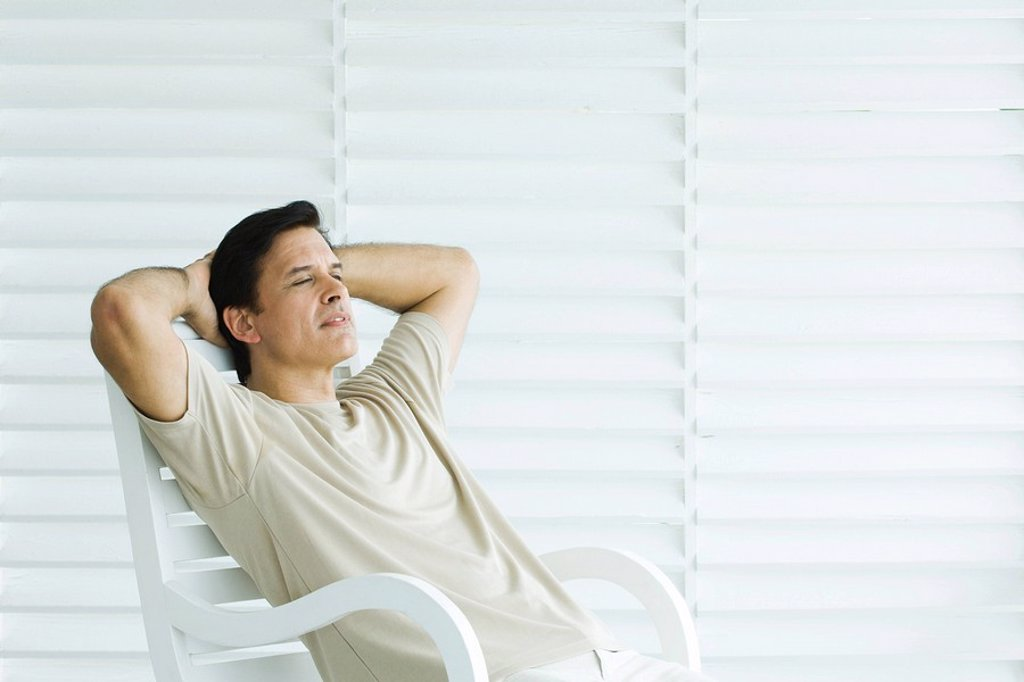Man sitting in chair with hands behind head, looking away : Stock Photo