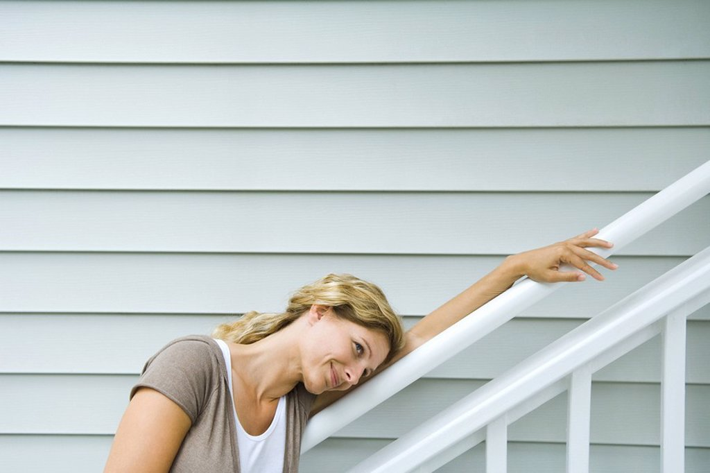 Woman leaning head against railing, smiling, looking away : Stock Photo