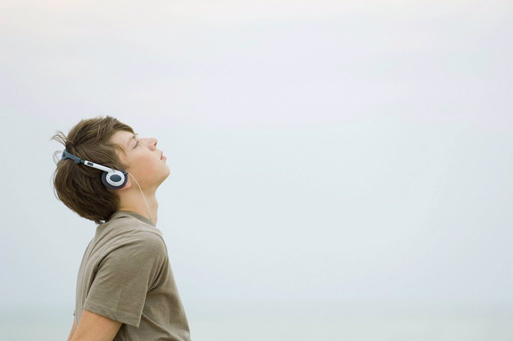 Teenage boy listening to headphones, looking up, side view : Stock Photo
