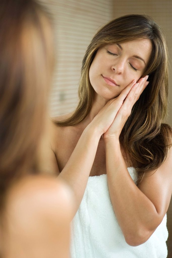 Stock Photo: 1569R-9033518 Woman standing in front of mirror with eyes closed, head resting on clasped hands, smiling