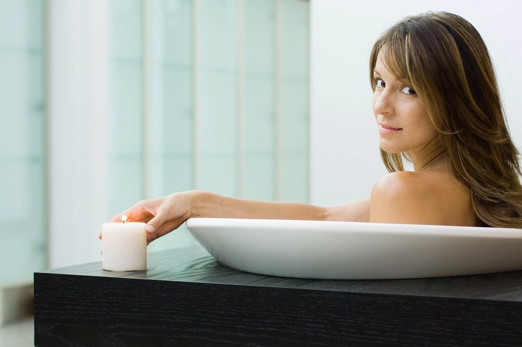 Woman sitting in bathtub, holding lit candle, smiling over shoulder at camera : Stock Photo