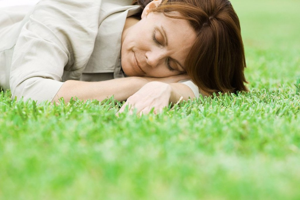 Woman lying on grass with head resting on arms, eyes closed : Stock Photo