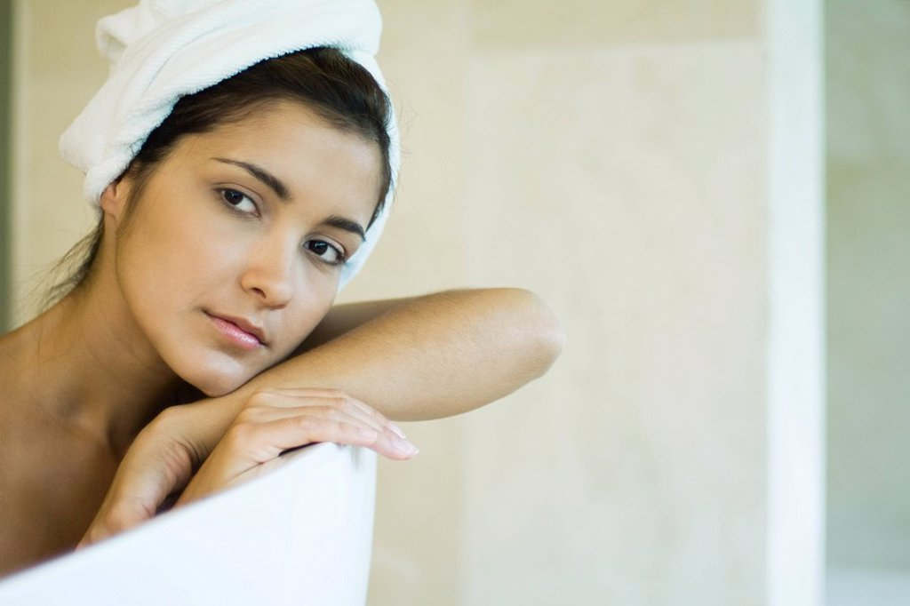 Woman resting head against side of bathtub, looking away, close-up : Stock Photo
