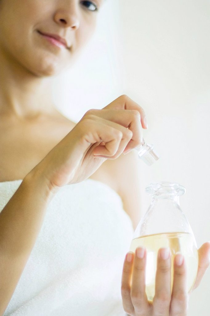 Stock Photo: 1569R-9033527 Woman wrapped in towel opening perfume bottle, smiling at camera, cropped view