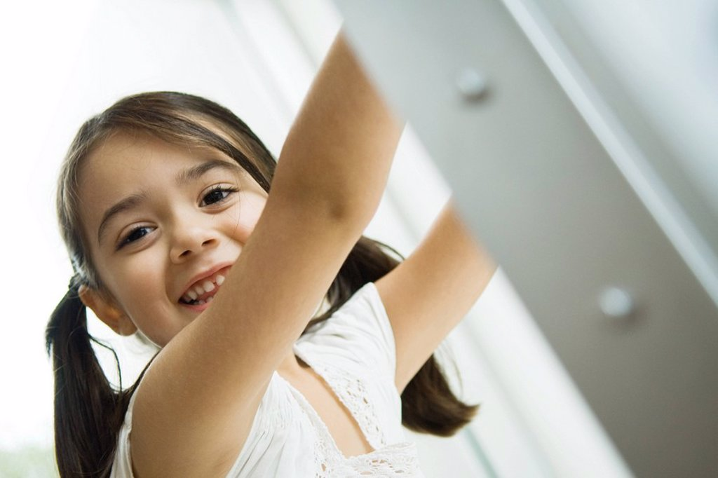 Little girl with pigtails smiling at camera, arms raised, portrait : Stock Photo