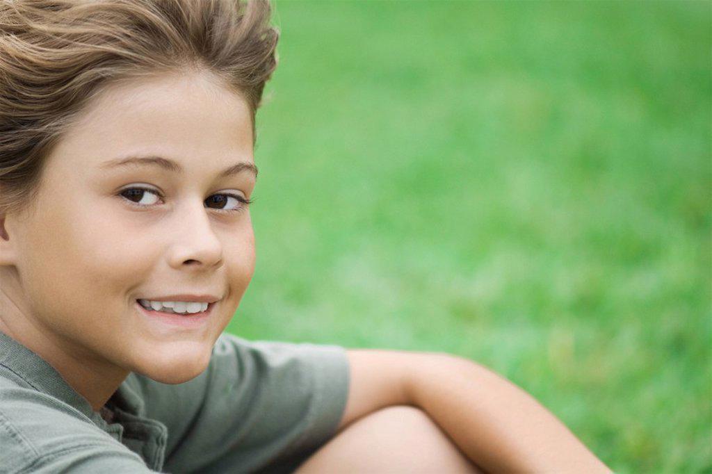 Boy sitting outdoors, smiling at camera, close-up : Stock Photo