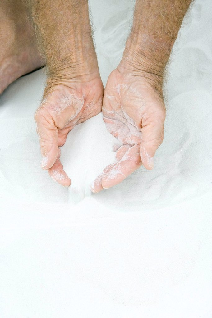 Stock Photo: 1569R-9033760 Man scooping sand in both hands, cropped view of hands