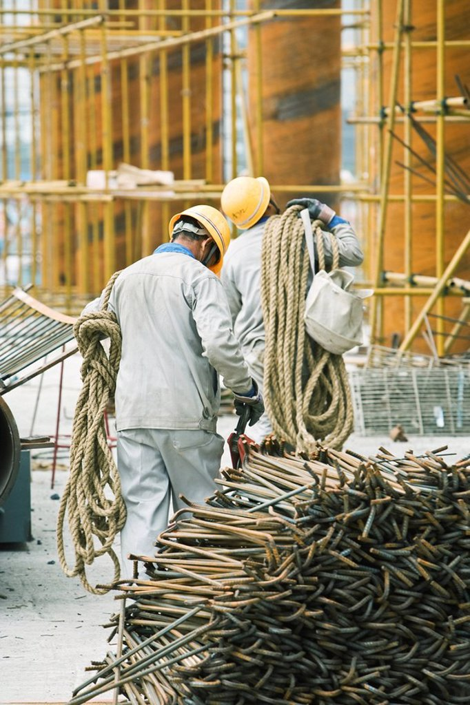 Workers at construction site carrying rope, metal rods stacked in foreground : Stock Photo