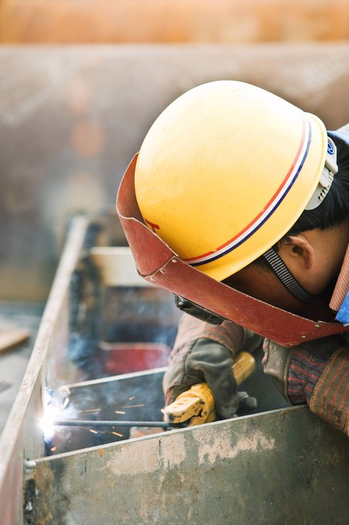 Worker welding metal, side view, close-up : Stock Photo