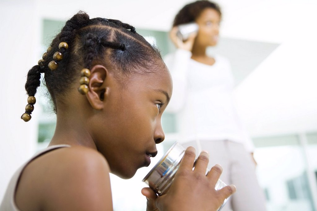 Little girl talking into tin can phone, mother listening in background, low angle view : Stock Photo