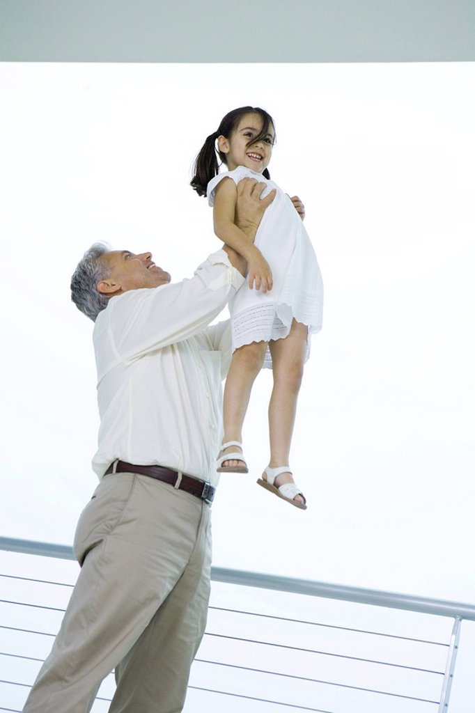 Grandfather holding granddaughter up in the air, both smiling, low angle view : Stock Photo