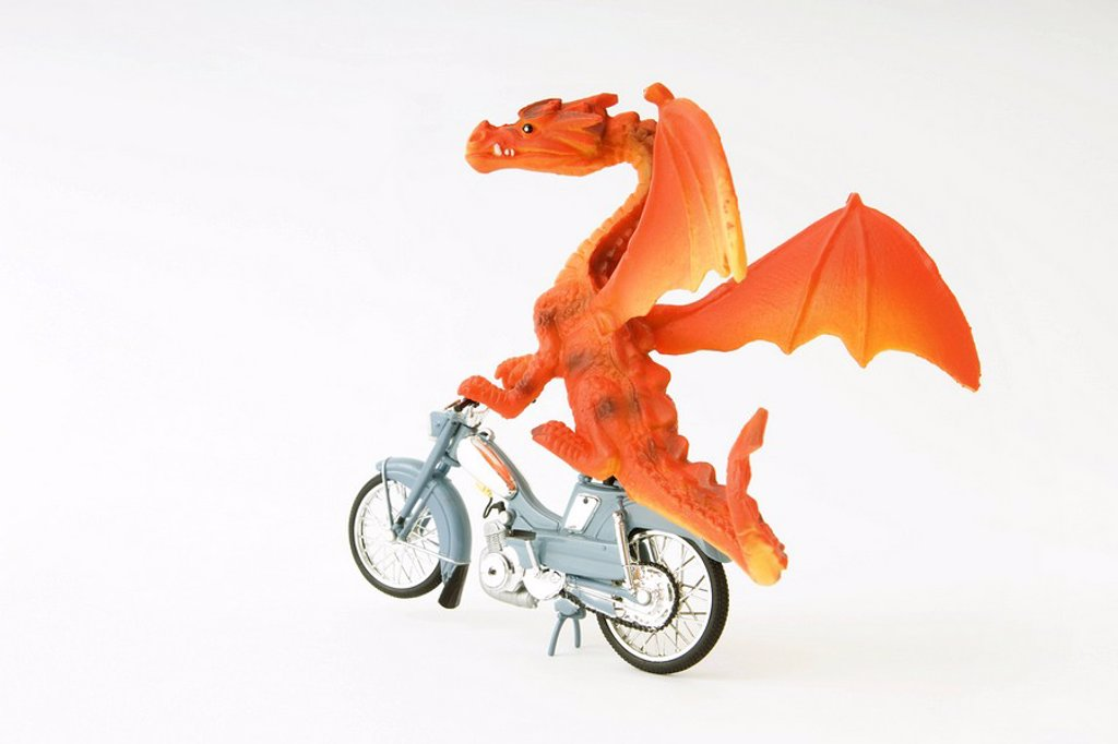 Toy dragon riding motorbike : Stock Photo