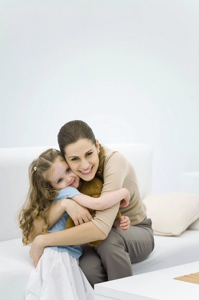 Young mother hugging little girl, smiling at camera : Stock Photo