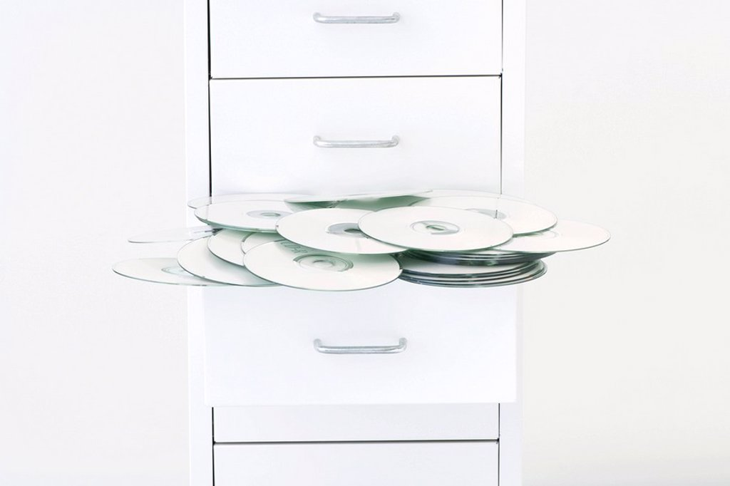 CDs spilling out of filing cabinet drawer : Stock Photo