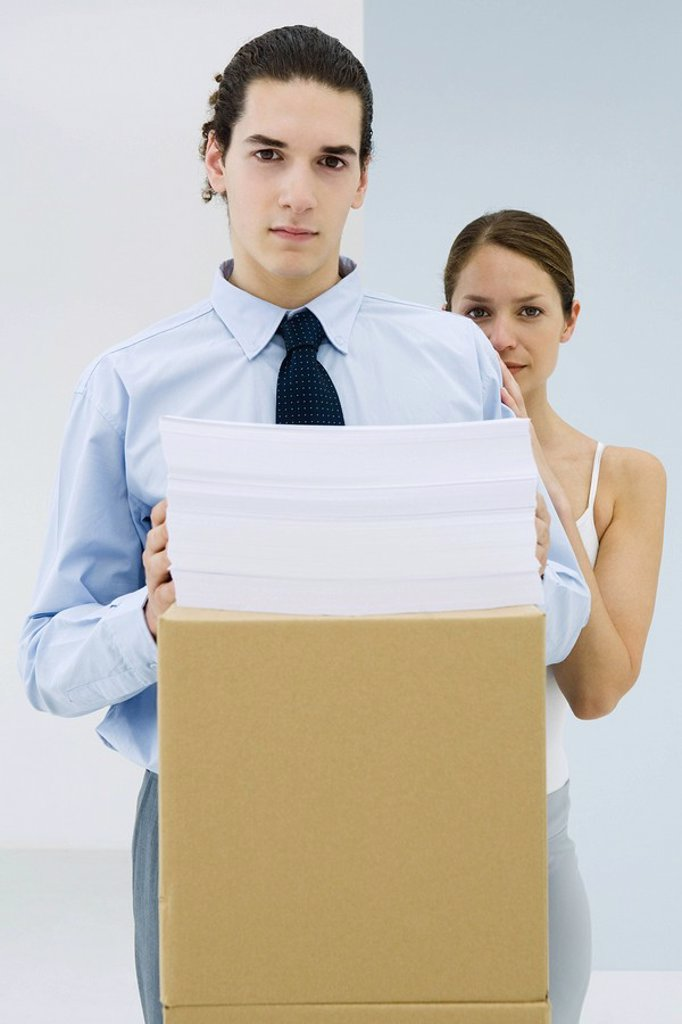 Stock Photo: 1569R-9034621 Young professional with documents stacked on cardboard box, woman standing behind him with her hand on his shoulder, both looking at camera
