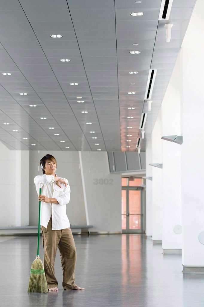Man standing in lobby with broom, listening to headphones : Stock Photo