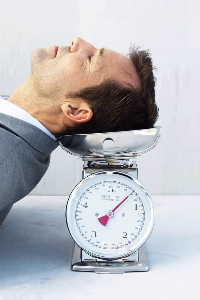 Man resting head on scale, eyes closed : Stock Photo