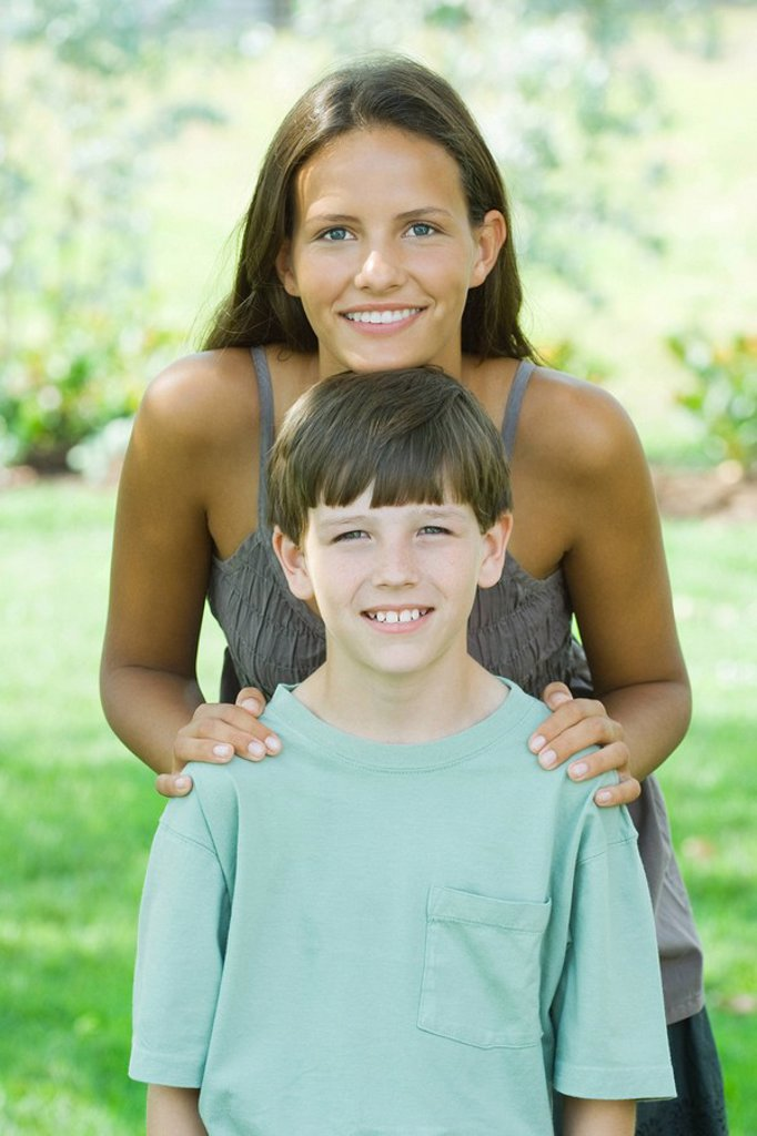 Teen girl standing behind younger brother, resting her chin on his head, both smiling at camera : Stock Photo