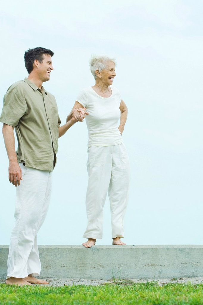 Senior woman standing on ledge, holding adult son´s hand, both looking away, smiling : Stock Photo