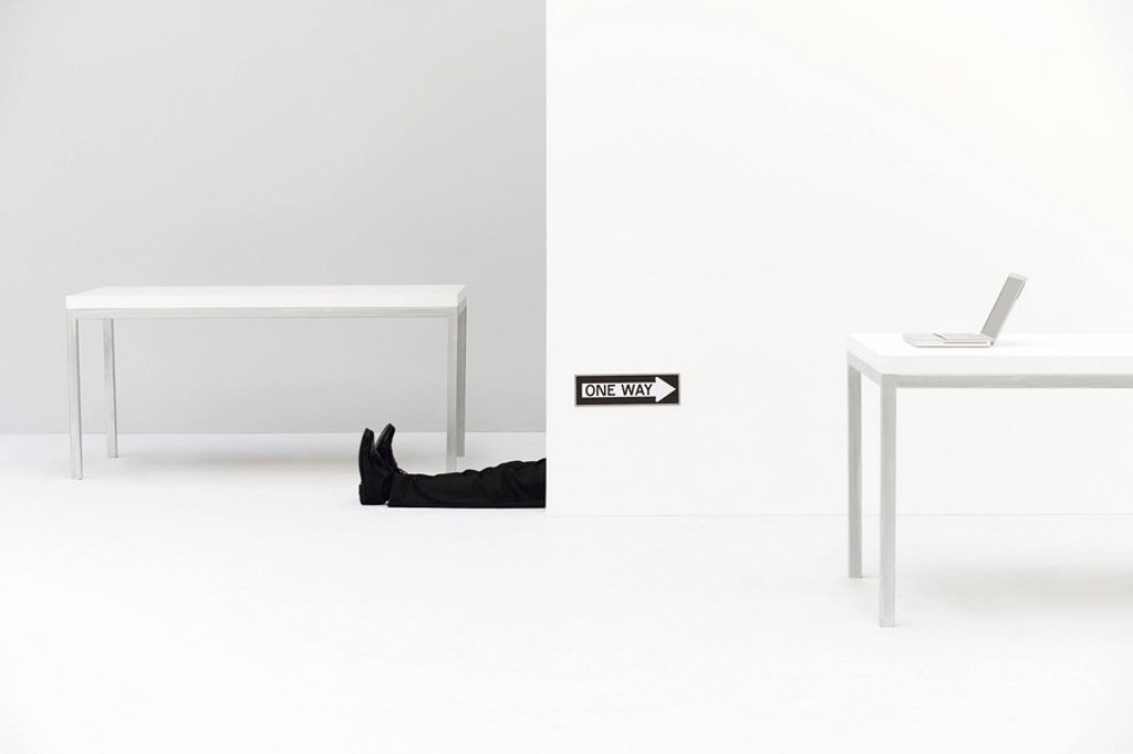 Stock Photo: 1569R-9035079 Businessman lying on the ground in office, one way sign pointing toward laptop computer on desk