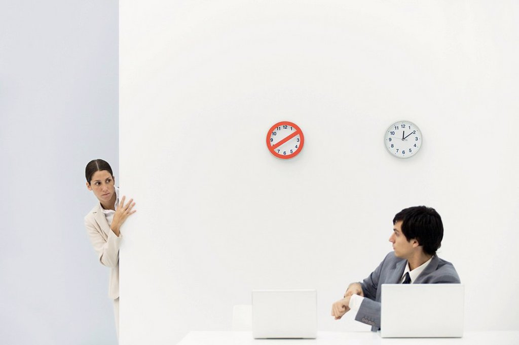 Stock Photo: 1569R-9035080 Woman peeking around corner as boss points at wristwatch, clocks on wall in background