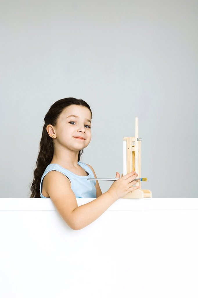 Stock Photo: 1569R-9035122 Little girl with small easel, smiling at camera