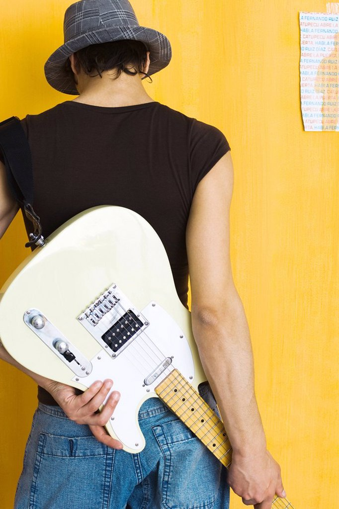 Young man holding electric guitar behind back, rear view : Stock Photo