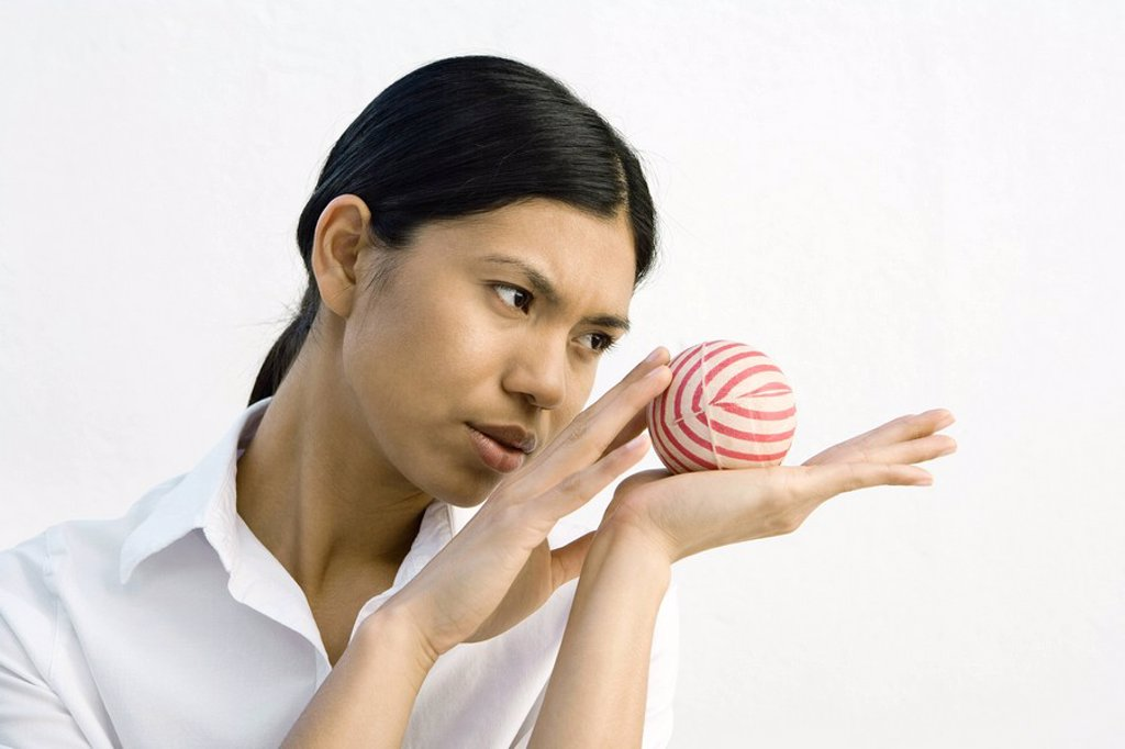 Stock Photo: 1569R-9035222 Woman holding striped ball in open palm, looking away