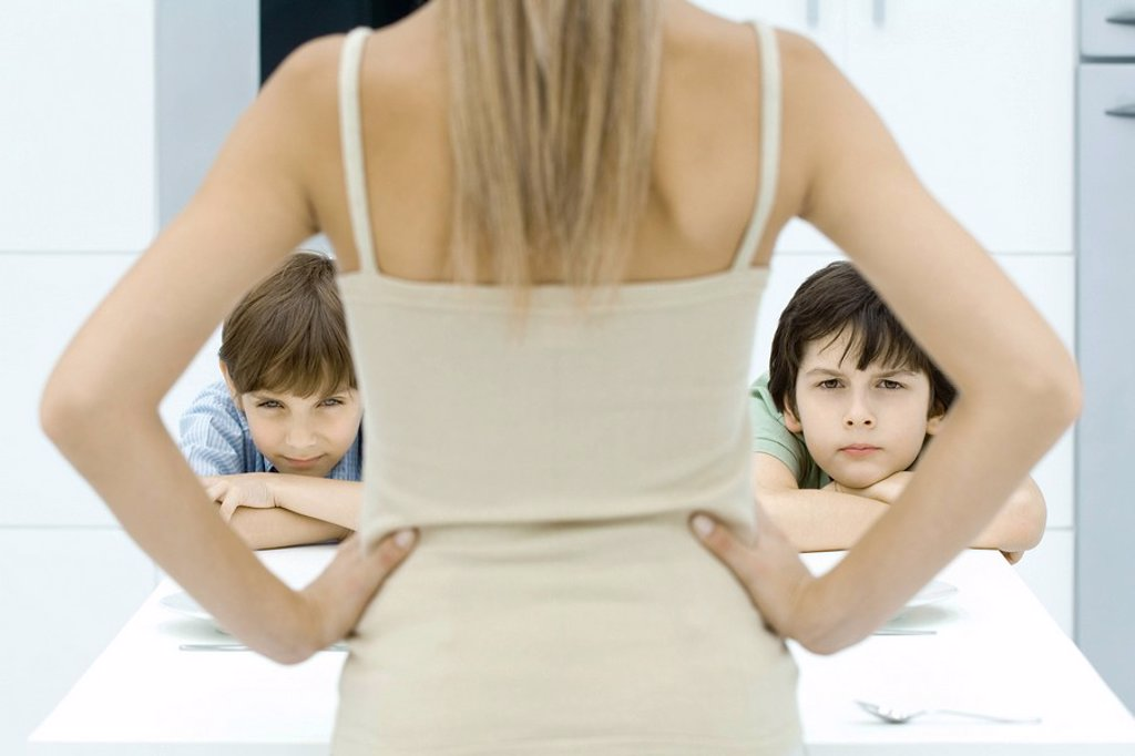 Stock Photo: 1569R-9035244 Boys pouting at kitchen table, being disciplined by mother, rear view