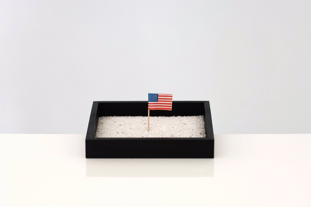 Tiny American flag in box of sand : Stock Photo