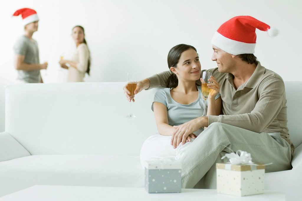 Couple sitting on sofa, drinking champagne, man wearing Santa hat : Stock Photo