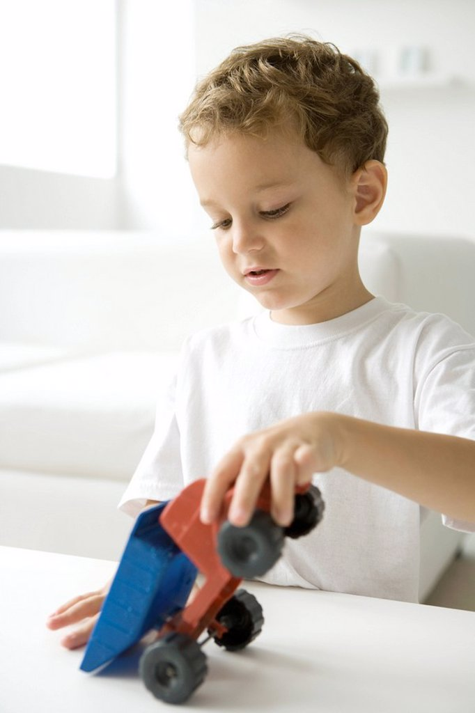 Little boy playing with toy dump truck : Stock Photo