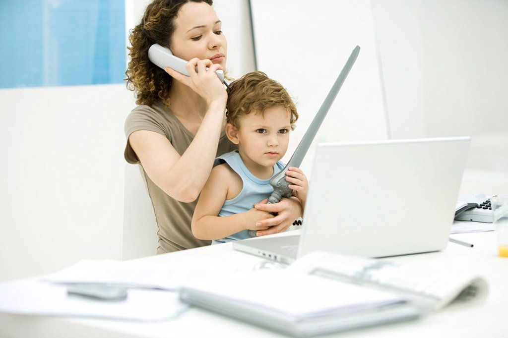 Stock Photo: 1569R-9035415 Young mother sitting at desk using phone while son sits on lap, holding sword