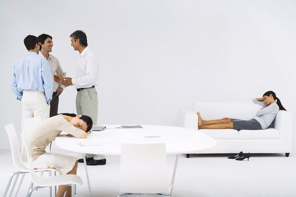 Women napping, one at table, one on couch, men talking in group in the corner : Stock Photo