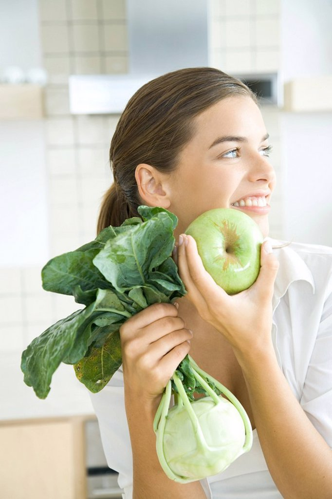 Stock Photo: 1569R-9035628 Woman holding apple and kohlrabi, looking away, smiling