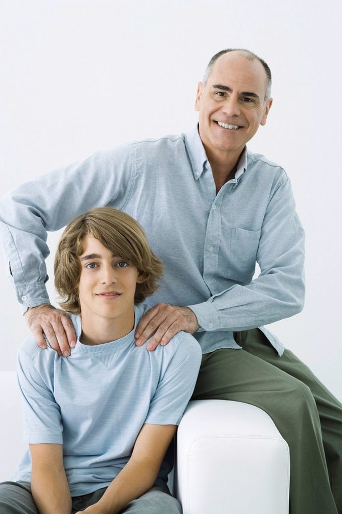 Father and son sitting on sofa, man´s hands on teen boy´s shoulders, portrait : Stock Photo