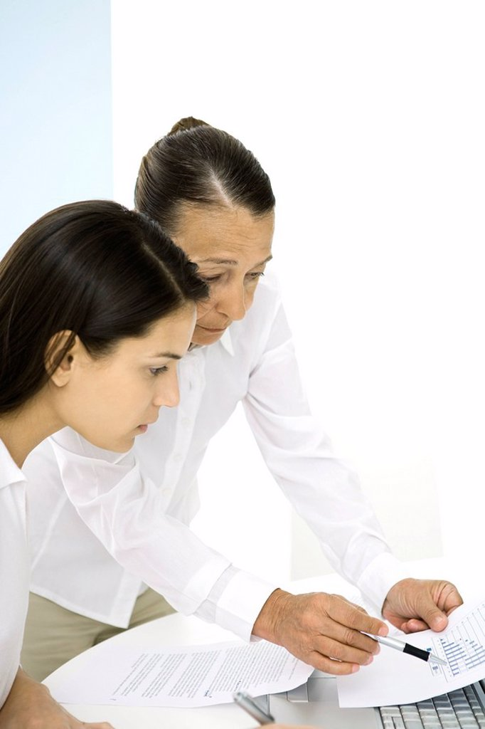 Senior woman in office, discussing document with younger colleague : Stock Photo