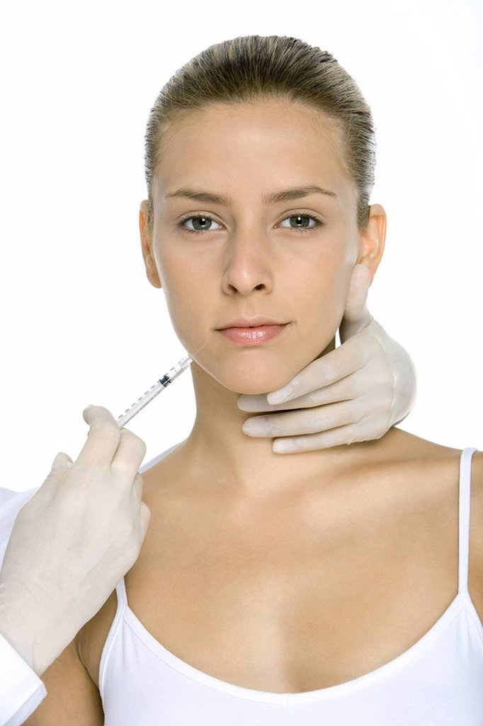 Young woman receiving collagen injection, looking at camera : Stock Photo