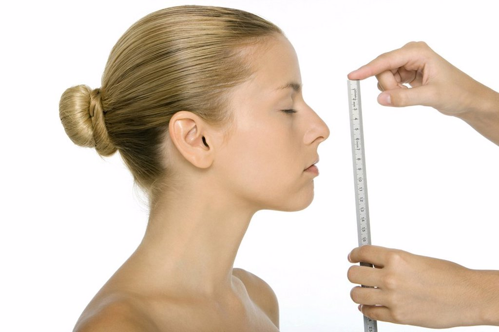 Woman in profile, face being measured with ruler : Stock Photo